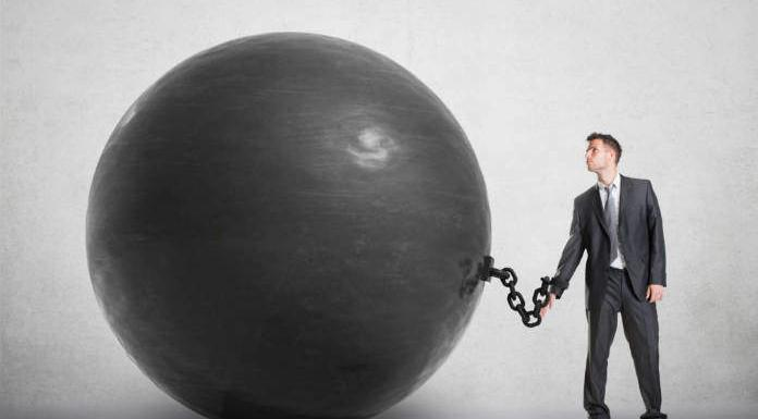 Man held back by a giant iron ball chained to his wrist / Concept of excuses
