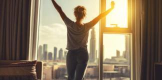 woman standing with arms at the window in morning / morning routine concept