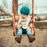 Co-parenting concept | estranged couple holding their child on a swing