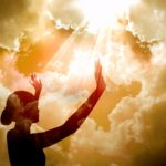 sihoette of woman against rays from sky: meeting god