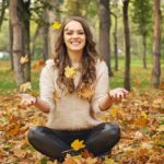 Beautiful happy young woman in the woods among autumn leaves | self-care concept