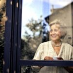 elderly woman smiling through the window with cup in hand