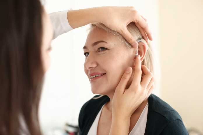 Senior woman trying on a hearing aid