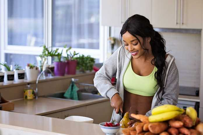 Happy young woman cutting fruits in the kitchen